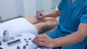 Doctor makes ultrasound of knee joint for man using ultrasound scanner.