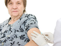 The doctor makes vaccination an old woman stock image