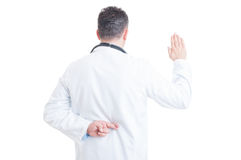 Doctor making false oath with crossed fingers behind back. Anonymous doctor or medic making false oath with crossed fingers behind back isolated on white Stock Image