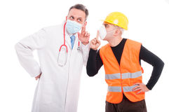 Doctor making listening gesture and constructor showing sush Royalty Free Stock Image