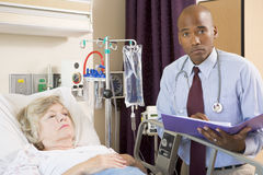 Doctor Making Notes About Patient,Looking Serious Stock Image