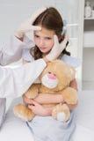 Doctor making plaster in little girl Stock Image