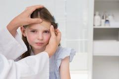 Doctor making plaster in little girl Stock Photos
