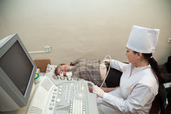 Doctor making ultrasound investigation stock photo