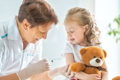 Vaccination to a child. A doctor making a vaccination to a child stock image