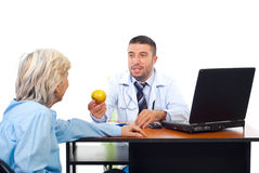 Doctor male offering apple to senior Stock Images
