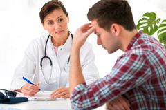Doctor with male patient. Doctor talking to her male patient at office Royalty Free Stock Photography