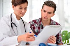 Doctor with male patient. Doctor talking to her male patient at office Royalty Free Stock Photo