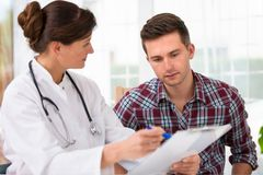 Doctor with male patient. Doctor talking to her male patient at office Stock Photos