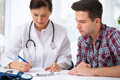 Doctor with male patient. Doctor talking to her male patient at office Stock Images