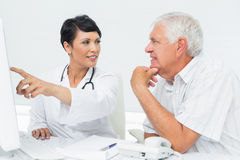 Doctor with male patient reading reports on computer Royalty Free Stock Photos