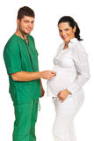 Doctor man examine pregnant woman Stock Image