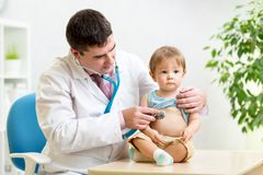 Doctor man examining heartbeat of kid boy with. Doctor men examining heartbeat of little boy with stethoscope Stock Images