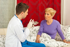 Doctor man explain to patient woman. Doctor men explain to senior sick women how to take the medicines and sitting on couch in home stock images