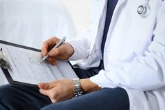 Free Doctor Man Filling Up Medical Form On Clipboard At Hospital, Close-up. Healthcare, Insurance And Medicine Concept Royalty Free Stock Photos - 144800038