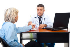 Doctor man give medicines to senior patient. Doctor man giving medicines and explanation to a senior woman patient in office,check also  Medical Royalty Free Stock Image
