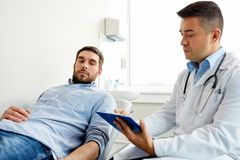 Doctor and man with health problem at hospital Royalty Free Stock Photos