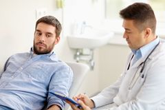 Doctor and man with health problem at hospital Stock Photos