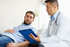 Doctor and man with health problem at hospital. Medicine, healthcare and people concept - doctor with clipboard and young male patient having health problem stock photos