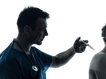 Doctor man holding hypodermic syringe silhouette Royalty Free Stock Photos