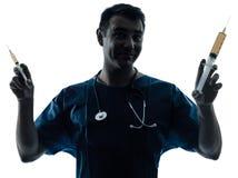 Doctor man holding hypodermic syringe silhouette portrait Stock Photos