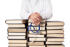 Doctor With Many Books. Senior doctor in white tunic and stethoscope leaning on many stacked books and textbooks Stock Photography