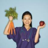 Doctor, manzana y zanahorias. fotografía de archivo