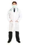 Doctor with mask on face and hands in pockets Stock Image