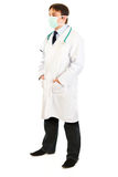 Doctor with mask on face and hands in pockets Stock Photos