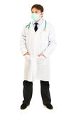 Doctor with mask on face and hands in pockets Stock Photo