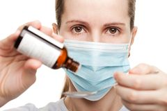 Doctor in mask holding medicine syrup Royalty Free Stock Photo