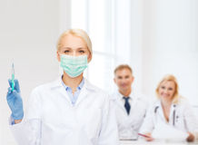 Doctor in mask holding syringe with injection Stock Photo