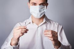 Doctor in mask with a injection syringe on the blue background royalty free stock images