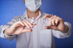 Doctor in mask with a injection syringe on the blue background stock photos