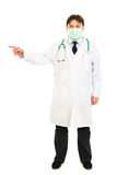 Doctor in mask pointing finger at something Stock Images