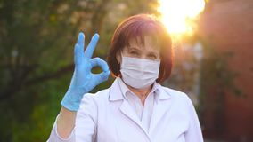 Doctor show OK sign. Doctor in mask show OK sign on sunset stock video