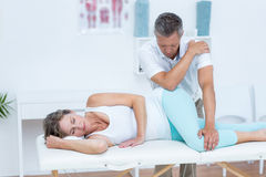 Doctor massaging his patient hip Royalty Free Stock Images