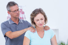 Doctor massaging his patient shoulders. In medical office Royalty Free Stock Photos