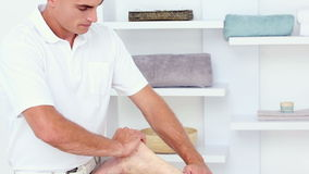 Doctor massaging his patients calf. In medical office stock footage