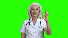 Doctor mayor de la mujer que muestra la muestra ACEPTABLE almacen de video