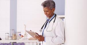 Doctor mayor negro feliz que se coloca en oficina con la tableta Foto de archivo