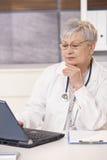Doctor mayor que mira el ordenador Fotografía de archivo libre de regalías