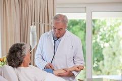 Doctor mayor que suena a su paciente imágenes de archivo libres de regalías