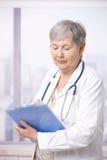 Doctor mayor que toma notas Fotografía de archivo