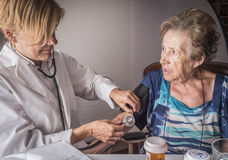 Doctor measures the arterial tension to oldster at home Stock Image