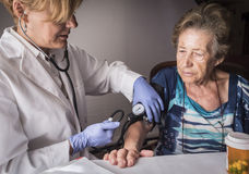 Doctor measures the arterial tension to oldster at home. Andalusia, Spain royalty free stock photo