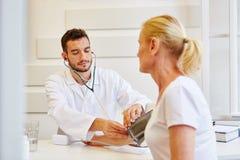 Doctor measures blood pressure Royalty Free Stock Image