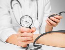 Doctor measures blood pressure by sphygmomanometer Royalty Free Stock Photos