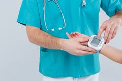 The doctor measures the girl`s pressure with an tonometer, pressing the buttons. Isolation. Close up. The doctor in the blue uniform measures the girl`s Stock Images