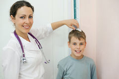 Doctor measures growth boy in medical office Stock Photo